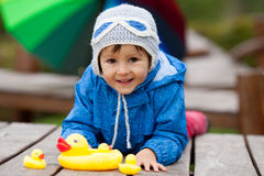 Adorable little boy, playing with rubber ducks outside on an aut Royalty Free Stock Photos