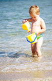 Adorable little boy playing in the sea Stock Photos