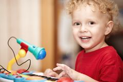 Adorable little boy playing with a toy microphone Stock Image