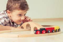 Adorable little boy playing with toys lying on the floor. Royalty Free Stock Photography