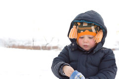Adorable little boy putting on his mittens Stock Image