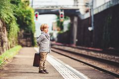 Little boy portrait. Adorable little boy on a railway station, waiting for the train with suitcase royalty free stock photo