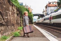 Little boy portrait. Adorable little boy on a railway station, waiting for the train with suitcase stock photography