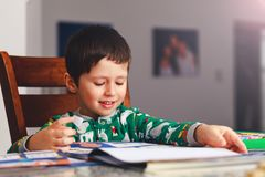 Adorable little boy reading book before going to sleep. Happy kid dressed in pajamas reads a story and amuses himself. Cute boy l. Earning to read next to stack stock image