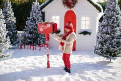 Adorable little boy with red hat and green glasses sending her letter to Santa, Christmas time stock images