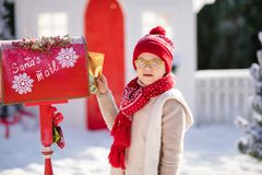 Adorable little boy with red hat and green glasses sending her letter to Santa, Christmas time royalty free stock photography