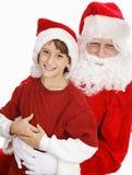 Adorable Little Boy on Santas Lap. Adorable little boy on Santa's lap, asking for Christmas presents. White background stock images