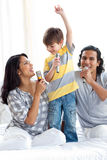 Adorable little boy singing with his parents. On a bed royalty free stock images