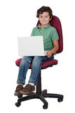 Adorable little boy sitting on big chair with lapt