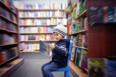 Adorable little boy, sitting in a book store Stock Photos