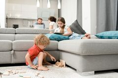 Family Members Wrapped up in Their Deeds. Adorable little boy sitting on carpet and playing with wooden toys while his elder sister lying on sofa and sketching royalty free stock photography