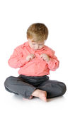 Adorable little boy sitting on the floor and Royalty Free Stock Image