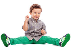 Adorable little boy sitting on the floor. Against white background Stock Photography