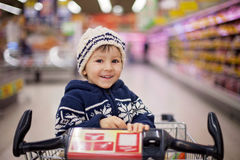 Adorable little boy, sitting in a shopping cart Royalty Free Stock Photo
