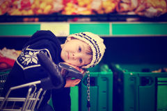 Adorable little boy, sitting in a shopping cart Royalty Free Stock Image