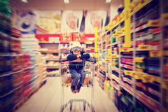 Adorable little boy, sitting in a shopping cart Stock Photos