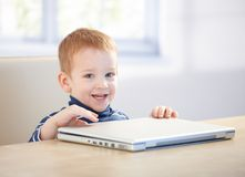 Adorable little boy smiling with laptop Royalty Free Stock Photos