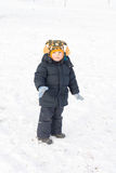 Adorable little boy standing in snow Stock Image