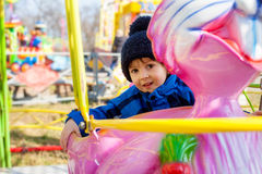 Adorable little boy, swinging on a pink rabbit Royalty Free Stock Image