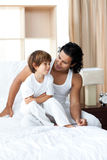 Adorable little boy talking with his father. Sitting on bed Royalty Free Stock Photo