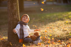 Adorable little boy with teddy bear in park on autumn day. Adorable little boy with teddy bear in the park on an autumn day in the afternoon, sitting on the Royalty Free Stock Photography