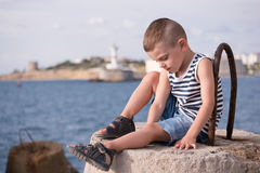 Adorable little boy in vest and shorts sitting against the sea in summer. Beautiful little boy in vest and shorts sitting on breakwater against the sea and shore Stock Photos
