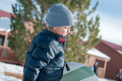 Adorable little boy walking in snow carrying sled with navy jack Stock Photography