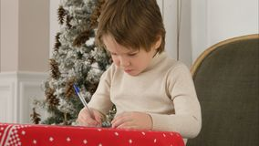 Adorable little boy writing a Christmas wishlist letter to Santa Claus. Professional shot on Lumix GH4 in 4K resolution. You can use it e.g. in your commercial Royalty Free Stock Photos