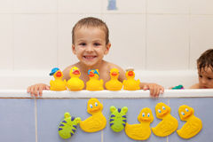 Adorable little boys in bathtub with his rubber duckies Royalty Free Stock Image
