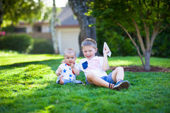 Adorable little brothers flying paper airplanes Royalty Free Stock Image