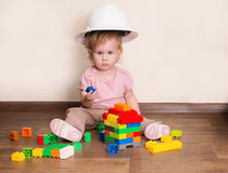 Adorable little builder. Cute baby in protective helmet playing Stock Image