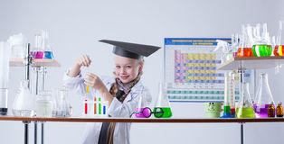 Adorable little chemist posing in lab with flasks Stock Photos