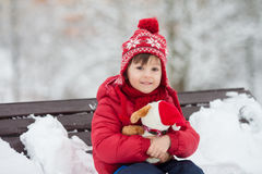 Adorable little child, boy, playing in a snowy park, holding ted. Dy bear, sitting on bench, wintertime stock photos