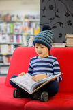 Adorable little child, boy, sitting in a book store Royalty Free Stock Photos