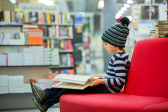 Adorable little child, boy, sitting in a book store Stock Photos