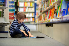 Adorable little child, boy, sitting in a book store royalty free stock image