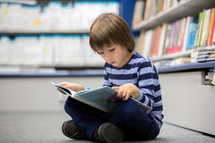 Adorable little child, boy, sitting in a book store Stock Photography