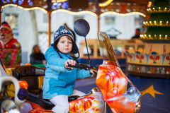 Adorable little child on a carousel at Christmas funfair or mark Stock Images