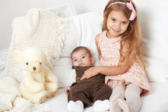 Adorable little child girl and boy sit in the bed with teddy bear Stock Image