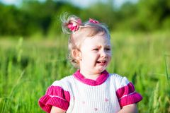 Adorable little child girl  cry on grass on meadow. Royalty Free Stock Photography