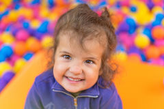 Adorable little child girl face closeup portrait. Happy child playing with color balls. Summer day. Funny cute child making vacati Stock Photography