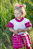 Adorable little child girl on grass on meadow. Royalty Free Stock Photo