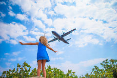 Adorable little child girl looking to the sky and flying plane directly above her. Beautiful exciting picture Royalty Free Stock Photos