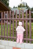 Adorable little child girl in park near fence in summer day Royalty Free Stock Photos