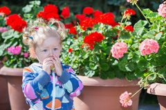 Adorable little child girl in park near flower Bed in summer day. Stock Image
