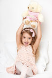 Adorable little child girl sit in the bed with her toy. The child girl hugs the teddy bear. Stock Images