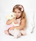 Adorable little child girl sit in the bed with her toy. The child girl hugs the teddy bear. Royalty Free Stock Image
