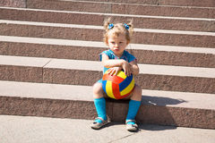 Adorable little child girl with toy ball on stairs . Stock Photos