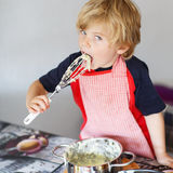 Adorable little child helping and baking apple pie in home''s ki Stock Photos