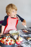Adorable little child helping and baking apple pie in home''s ki Royalty Free Stock Photo